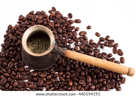 Jazva, small pot for making coffee. Many coffee beans in the background. Texture of the coffee beans on a white background. Smelly, saturated brown arabic coffee beans - stock photo