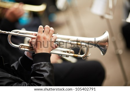 jazz band playing on the street, selective focus on the hands with trumpet - stock photo