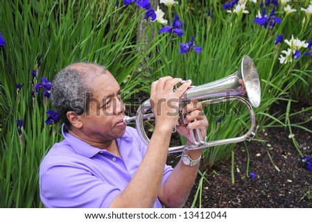 Jazz musician playing in a nature garden with his musical instrument. - stock photo