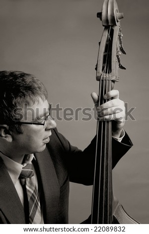 Jazz musician playing upright bass in black and white - stock photo