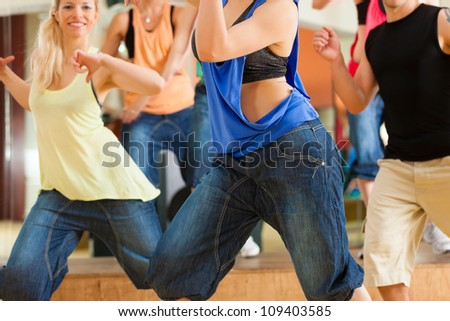 Jazzdance - young people dancing in a studio or gym doing sports or practicing a dance number - stock photo