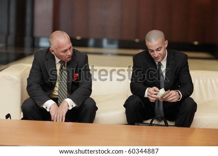 Jealous businessman looking at the other businessman counting his money