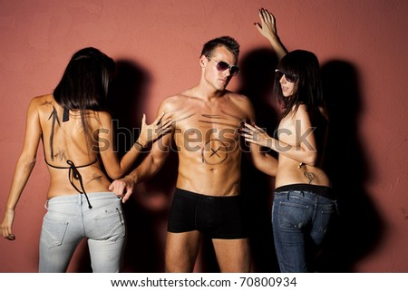 Jealous people. Handsome man pulled by two sexy woman