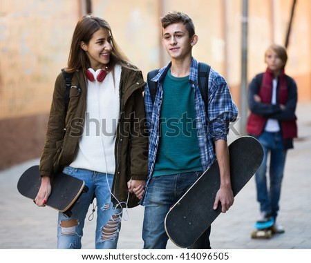 Jealous teen and his smiling spanish  friends after conflict outdoors  - stock photo