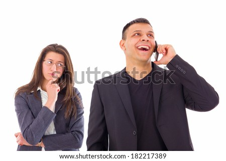 jealous woman looking at her man talking on the phone like he is cheating on her - stock photo