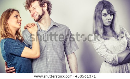 Jealousy and betrayal concept. Abandoned jelous girl watching on happy hugging couple. Triangle relationship. - stock photo