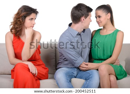 Jealousy. Young sad women sitting on the couch with her arms crossed while another women and men hugging near her - stock photo