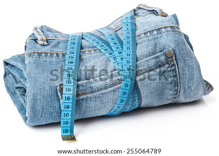 Jeans and a measuring tape on white background - stock photo