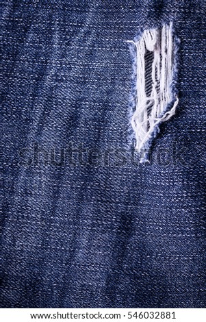 Jeans background. Texture. The holes in the fabric.