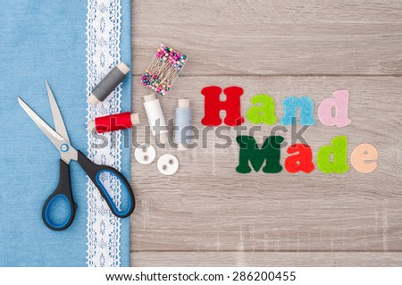 Jeans fabric for sewing, lace, accessories for needlework and inscription Handmade of felt on old wooden background. Spool of thread, scissors, buttons, sewing supplies. Set for needlework top view - stock photo