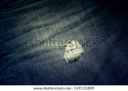 Jeans fabric texture, detail of torn trousers, textile textured background