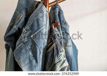 Jeans hanger on wooden rack in front of a white wall and light from window. - stock photo