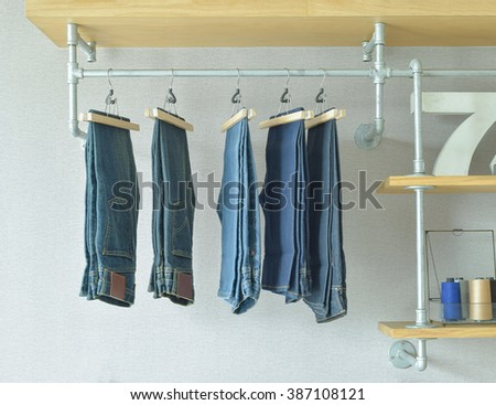 jeans hanging in industrial style walk in closet - stock photo
