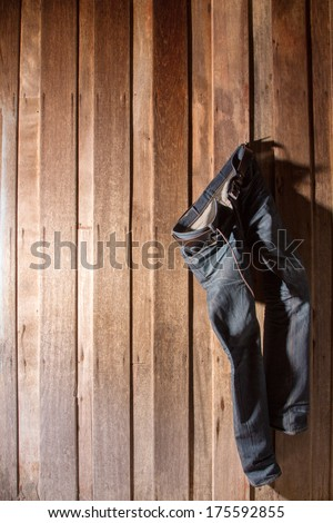 Jeans hanging wooden wall - stock photo