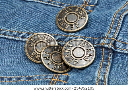 Jeans metal buttons on denim. Macro shoot. - stock photo