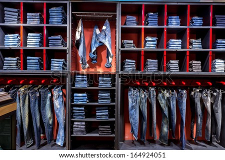 Jeans shirts at shelf in shop - stock photo