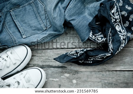 jeans,sneakers and bandanna on floor - stock photo