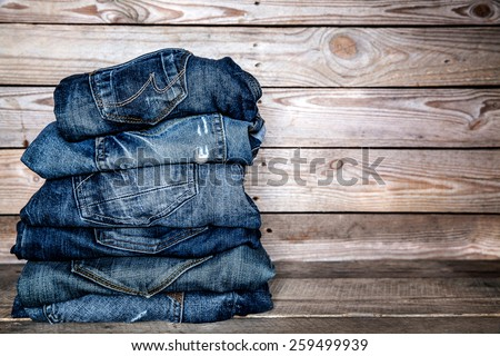 jeans stacked on a wooden background - stock photo