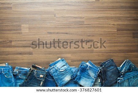 Jeans stacked on a wooden background, View from above with copy workspace - stock photo