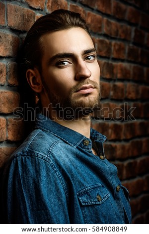 Jeans style. Portrait of a handsome young man in jeans clohes standing against the brick wall. Men's beauty, fashion. Men's barbershop, Hairstyle.