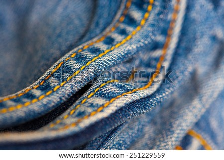 Jeans with yellow stitching thread close up, small depth sharpness - stock photo
