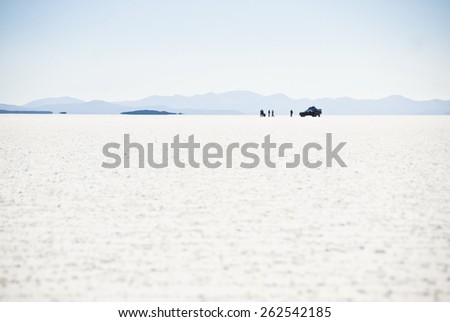 Jeep with tourists in the salt desert Uyuni, Bolivia. - stock photo