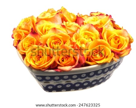 Jellow orange roses in a heart bowl - stock photo