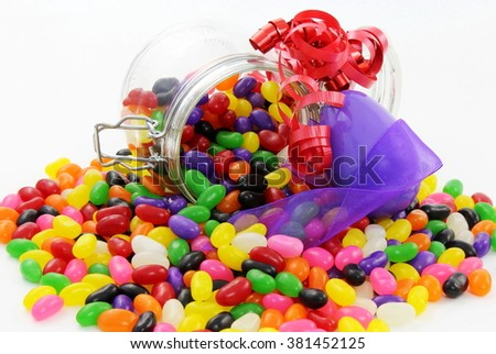 Jelly Beans in Glass Jar with large Purple plastic Easter Egg and Purple and Red Ribbon - stock photo