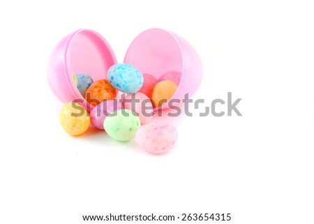 Jelly beans in plastic egg for easter over white background. - stock photo