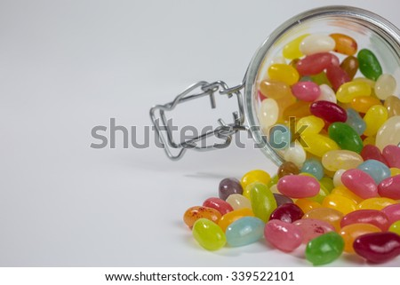 jelly beans of different colors and flavors in a glass jar - stock photo