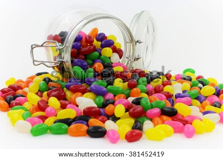 Jelly Beans spilt from Glass Jar with Open Lid and Metal Clasp II - stock photo