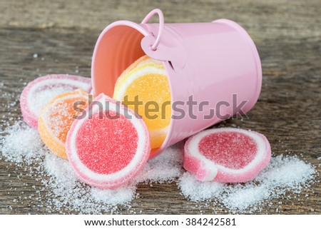 Jelly sweet, flavor fruit, candy dessert colorful on wooden background, and small pink bucket. - stock photo
