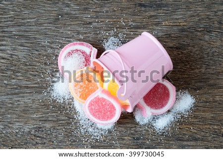 Jelly sweet, flavor fruit, candy dessert colorful on wooden background, and small pink bucket. - Vintage filtered style. - stock photo