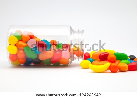 Jellybean sugar candy snack fall from a glass container - stock photo