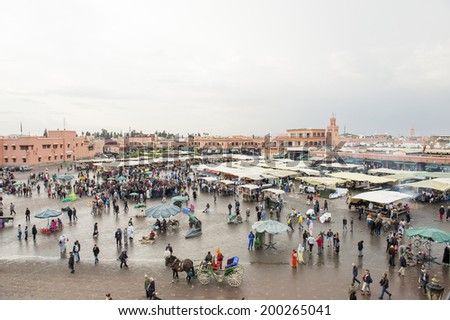 JEMMA DAR FNA, THE MAIN BAZAAR, MARRAKECH, MOROCCO, MAY 11, 2014. Horse wagons and people strolling around the booths and stalls in Jemma Dar Fna,  Marrakech, Morocco, on May 11th, 2014. - stock photo