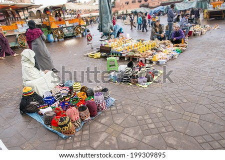 JEMMA DAR FNA, THE MAIN BAZAAR, MARRAKECH, MOROCCO, MAY 11, 2014. People selling objects on the ground in Jemma Dar Fna,  Marrakech, Morocco, on May 11th, 2014.  - stock photo