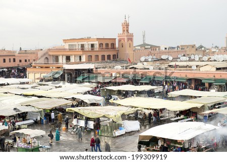 JEMMA DAR FNA, THE MAIN BAZAAR, MARRAKECH, MOROCCO, MAY 11, 2014. People strolling around the booths and stalls on a rainy day in Jemma Dar Fna,  Marrakech, Morocco, on May 11th, 2014. - stock photo