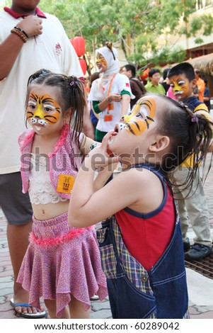 JENJAROM, MALAYSIA - CIRCA FEBRUARY 2010:Unidentified children with their face painted with tiger graffiti during the Chinese New Year event at a temple circa February 2010 in Jenjarom, Malaysia - stock photo