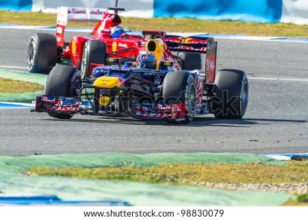 JEREZ DE LA FRONTERA, SPAIN - FEB 09: Sebastian Vettel of Red Bull F1 followed by  Fernando Alonso of Scuderia Ferrari races during a training session on February 09, 2012, in Jerez de la Frontera, Spain - stock photo