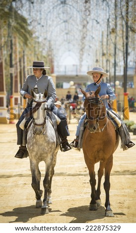JEREZ DE LA FRONTERA, SPAIN-MAY 17: People mounted on horse and dressed in typical Andalusian costume, on fair ride on May 17, 2014 in Jerez de la frontera. - stock photo