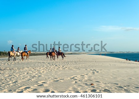 Jericoacoara, Ceara state, Brazil - July 18, 2016: Tourists ride on horseback at Sunset Dune about an hour before sunset