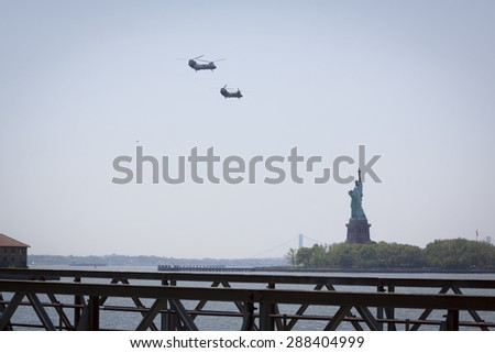 JERSEY CITY, NJ - MAY 26 2015: US Marine Corps helicopters fly past the Statue of Liberty on the Upper New York Bay before the USS San Antonio departs Pier 92 at the end of Fleet Week NY 2015. - stock photo