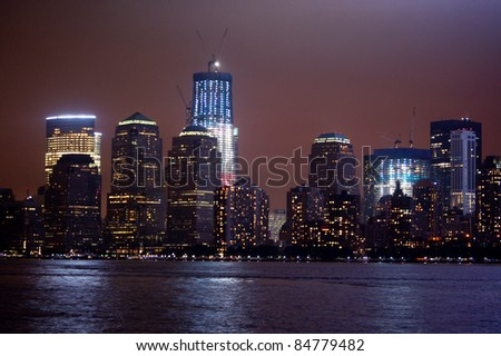 JERSEY CITY, NJ - SEPTEMBER 11:The new World Trade Center rises in red, white and blue over the New York City skyline on September 11, 2011.  Currently at 80 stories, the tower will rise to 105 floors