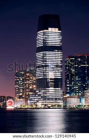 Jersey City skyline with skyscrapers at night over Hudson River viewed from New York City Manhattan downtown. - stock photo
