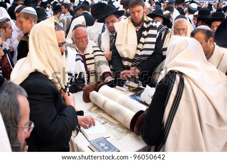 JERUSALEM - APRIL 05: A group orthodox religious Jews wearing a prayer shawl  around the Torah scroll celebrate the Jewish Pesach (Passover) at the Wailing Wall on April 05 2007 in Jerusalem. - stock photo