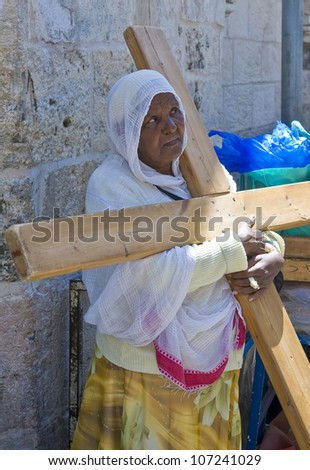 JERUSALEM - APRIL 13 : Ethiopian Christian pilgrim carry across along the Via Dolorosa in Jerusalem on April 13 2012 commemorating the path Jesus carried his cross on the day of his crucifixion