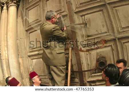 JERUSALEM - APRIL 21: Member of family, that stores the keys of the Holy Sepulchre, open the door to the Holy Sepulchre, on Good Friday April 21 2006 in Jerusalem, Israel.