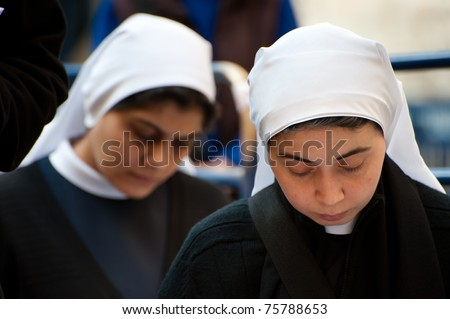 JERUSALEM - APRIL 22: Palestinian Catholic nuns pray outside of the Church of the Holy Sepulcher in Jerusalem on Good Friday, April 22, 2011.