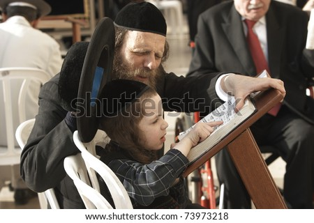 JERUSALEM - APRIL 4: Unidentified dad teaching his unidentified son from the Hebrew holy books on April 4, 2008 in Jerusalem.