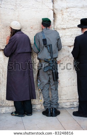 JERUSALEM - AUGUST 21: An Israeli soldier prays among other worshipers at the Western Wall, the holiest site in Judaism, in the Old City of Jerusalem on Aug. 21, 2011.